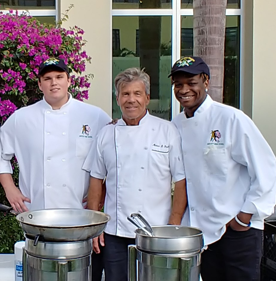 Three men in chef's jackets stand outside behind a table with cooking implements.